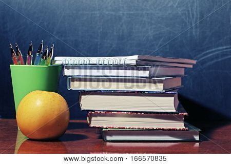Still life with school books and apple against blackboard toned with a retro vintage warm like filter