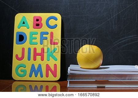 Still life with school books and apple against blackboard