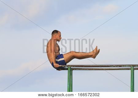 guy playing sports on parallel bars against the sky blue shorts