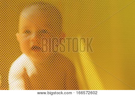child sitting in the playpen for children on a sunny day family chores busy child smile