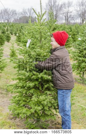 Boy hugging the perfect Christmas tree found on outdoor tree farm