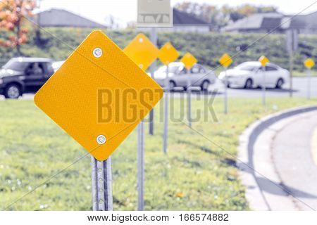 Yellow traffic signs along the turn of a highway on ramp with cars in the background