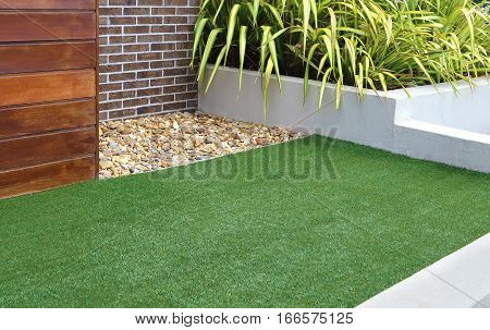 Combination of timber plants rocks artificial grass brick and render wall