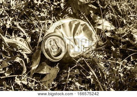 Crushed soda can lying in grass - sene colored in sepia tone
