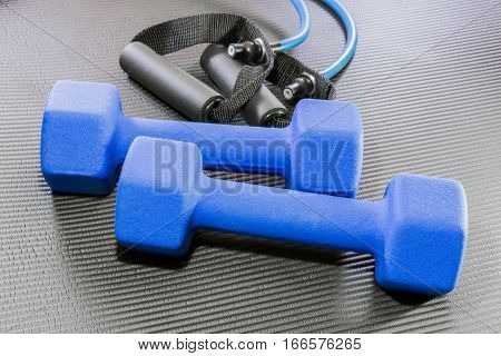 Blue dumbbell weights and resistance bands lying on a black open yoga exercise mat