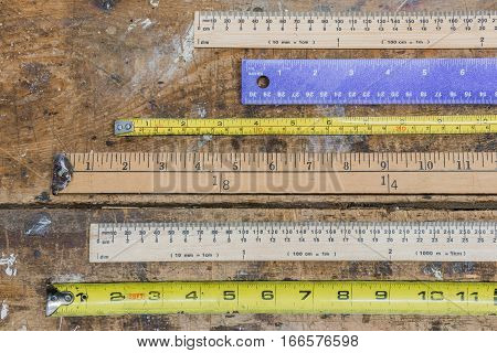 Various measuring sticks rulers tape measures layed out on scratched workshop table in linear pattern