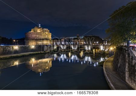 Night view of Rome Castle Sant Angelo (Mausoleum of Hadrian) and bridge Sant Angelo over the river Tiber in Roma Italy.