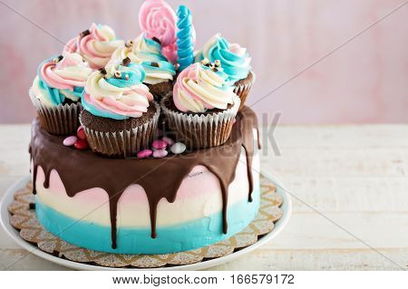 Pink and blue festive cake with chocolate glaze for a birthday or baby shower