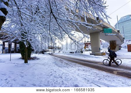 PORTLAND OR - JANUARY 11: Man crosses the street with a bicycle in the snow in Portland OR on January 11 2017