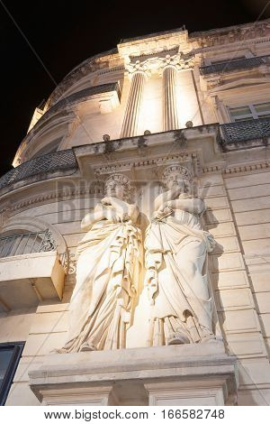 Montpellier, France- September 29, 2016: Architectural detail low angle point of view at night, two women in stone on Beaux arts style Gaumont theater building, Place de le Comedie Montpellier France