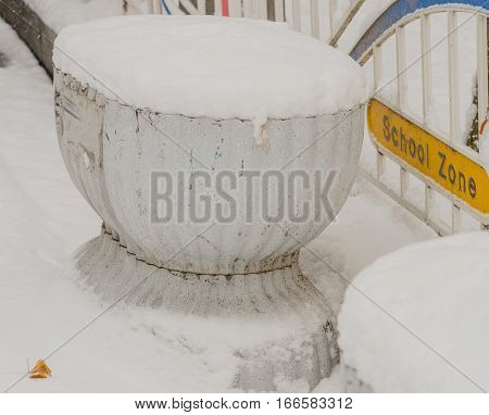White flower planter covered in snow sitting on a street next to a fence