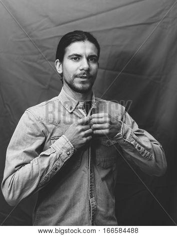 Trendy guy buttons denim shirt. Portrait of a Man in denim jacket