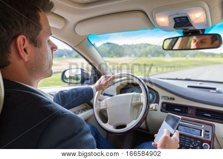 Businessman using cell phone and texting while driving not paying attention to the road.