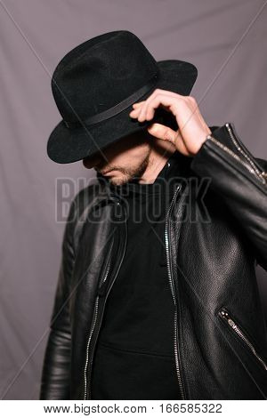 Portrait of young trendy guy in a hat and leather jacket