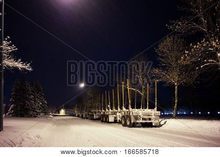Two eighteen wheel trucks with attached empty log trailers parked along the edge of a street under street lights at night in winter