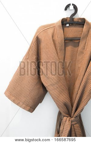 Bathrobe brown hung in room white background.