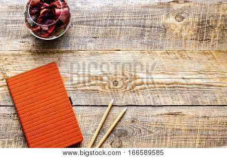 composition of orange notebook with pencil and flower sachets on wooden table