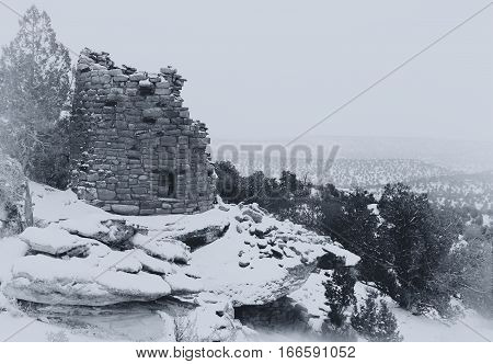 Painted Hand Tower an Anasazi ruin overlooking Hovenweep Canyon during a snow storm.