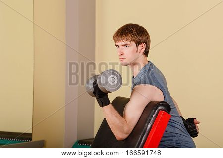 Man doing exercise for biceps with hand weights. Working with free weight. Healthy lifestyle concept. Fitness.
