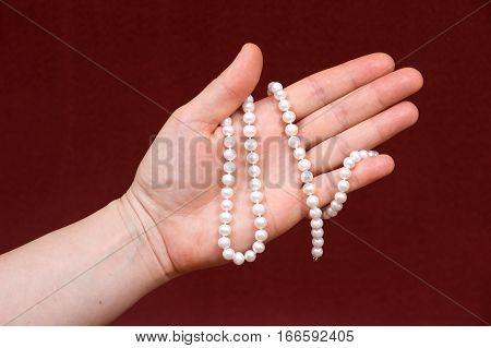 Young woman holding string of beautiful shiny small freshwater white pearl beads on red fabric background