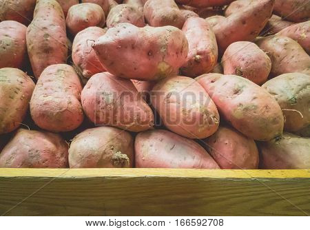 Stack of Potatoes on Fruit Shelf Stand with Wood for Copy Space at bottom