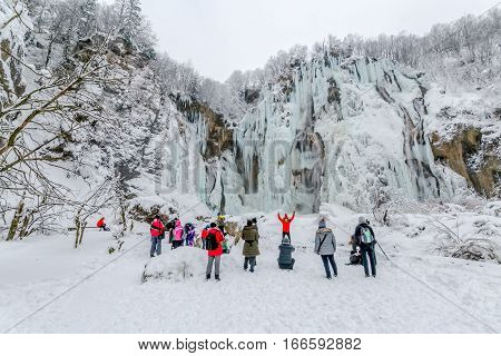 PLITVICE LAKES, CROATIA - January 21, 2017: The group of tourists enjoying the view of the frozen large waterfall in snowy winter.