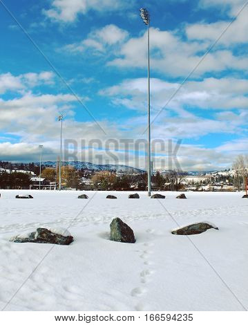 Winter landscape scene of outdoor snow covered sports field with foot tracks and tall stadium lights in field. Large rocks in foreground.Mountains trees bright blue sky and white clouds in background.