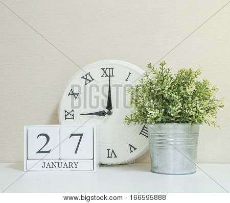White wooden calendar with black 27 january word with clock and plant on white wood desk and cream wallpaper textured background selective focus at the calendar