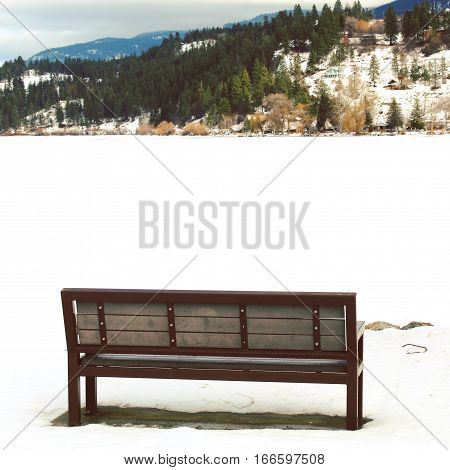 Empty park bench isolated on winter landscape. Bench overlooking frozen snow covered lake with forest hill and mountains in background.