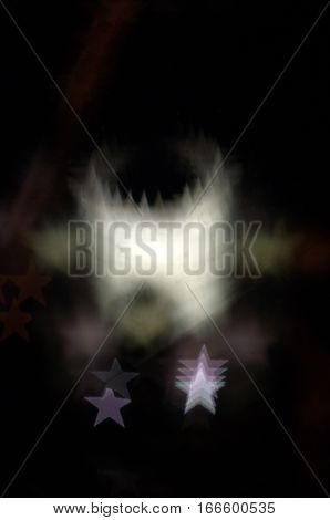 multiple white five pointed stars bunched together in a circular formation with a dark background bokeh effect