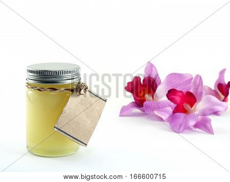 yellow balm in transparent glass bottle with blank brown paper label and artificial orchid flowers on white background, ointment for topical to relieve the pain