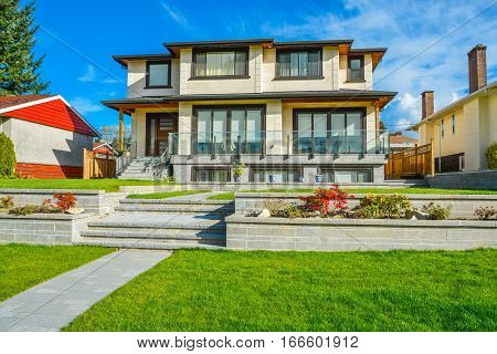 New luxury residential house with land terraces over front yard. Single family house on blue sky background