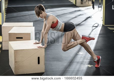 Sexy girl leans on the wooden box with her hands and holds the left leg bent in the knee in the gym. She wears a black shorts, red top and sneakers, gray sleeveless. Horizontal.