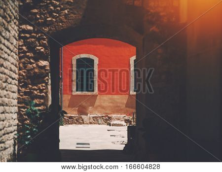 Single old arc window on red wall of facade of residential house in Barcelona Born district on sunny day view from stone archway
