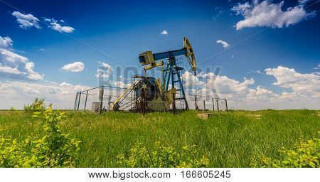 Oil field with pump jack, profiled on blue sky with white clouds, on a sunny day