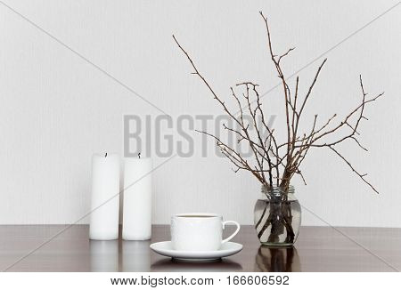 Minimalistic still life with cup candles and branches in bottle on a wooden table. Romantic grey and white stylish interior still life