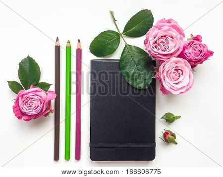 Colorful minimalistic composition with black sketchbook pink roses and pencils. Flat lay on white table top view
