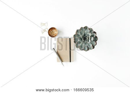 Feminine home office workspace with succulent diary and golden clips on white background. Flat lay top view