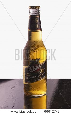 JANUARY 192017: Miller beer bottle over black reflecting background isolated over white background. Miller is one of main beer brands in the world