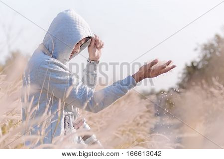Mysterious Handsome Man In White Hoodie Standing In The Grass Field.