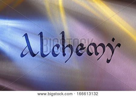 Handwritten word alchemy in medieval latin script under colored lights. English language.