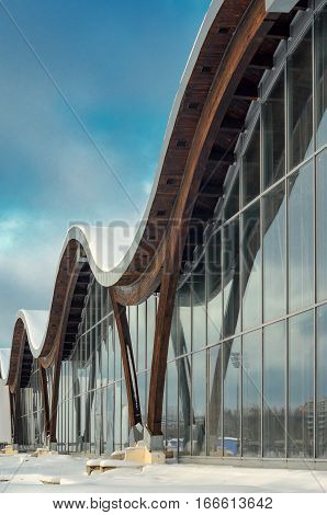 MINSK BELARUS - January 15 2017: Sports complex Olympic reserve. Pool National Olympic Training Center in athletics in Minsk Belarus. Element of modern building with circular shape facade against blue sky. Design of arched roof and stained glass system.