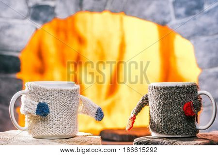 Tea mugs in sweater cozies give hands to each other. Fire hearth on the background
