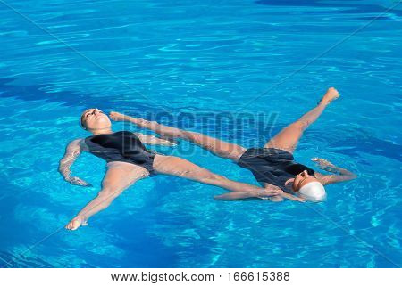 Synchronized swimming duet performing their routine, toned image,