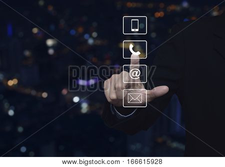 Businessman pressing telephone mobile phone at and email buttons over blur colorful night light city tower Customer support concept