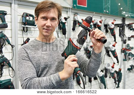 Man With Perforator In Hardware Store