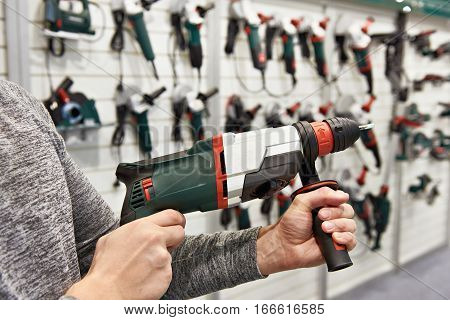 Man With Electrical Perforator In Hardware Store