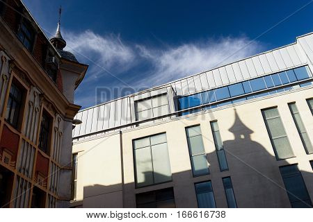 The shadow of an old house with a spire on the roof on the wall of a modern building on a background of blue sky with clouds in Riga