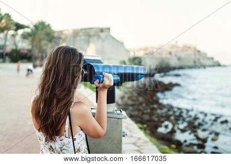 Young Girl Looking Through A Coin Operated Binoculars On The Sea Shore Of Antibes, France