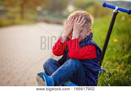 Little boy crying fell from the scooter in open air.